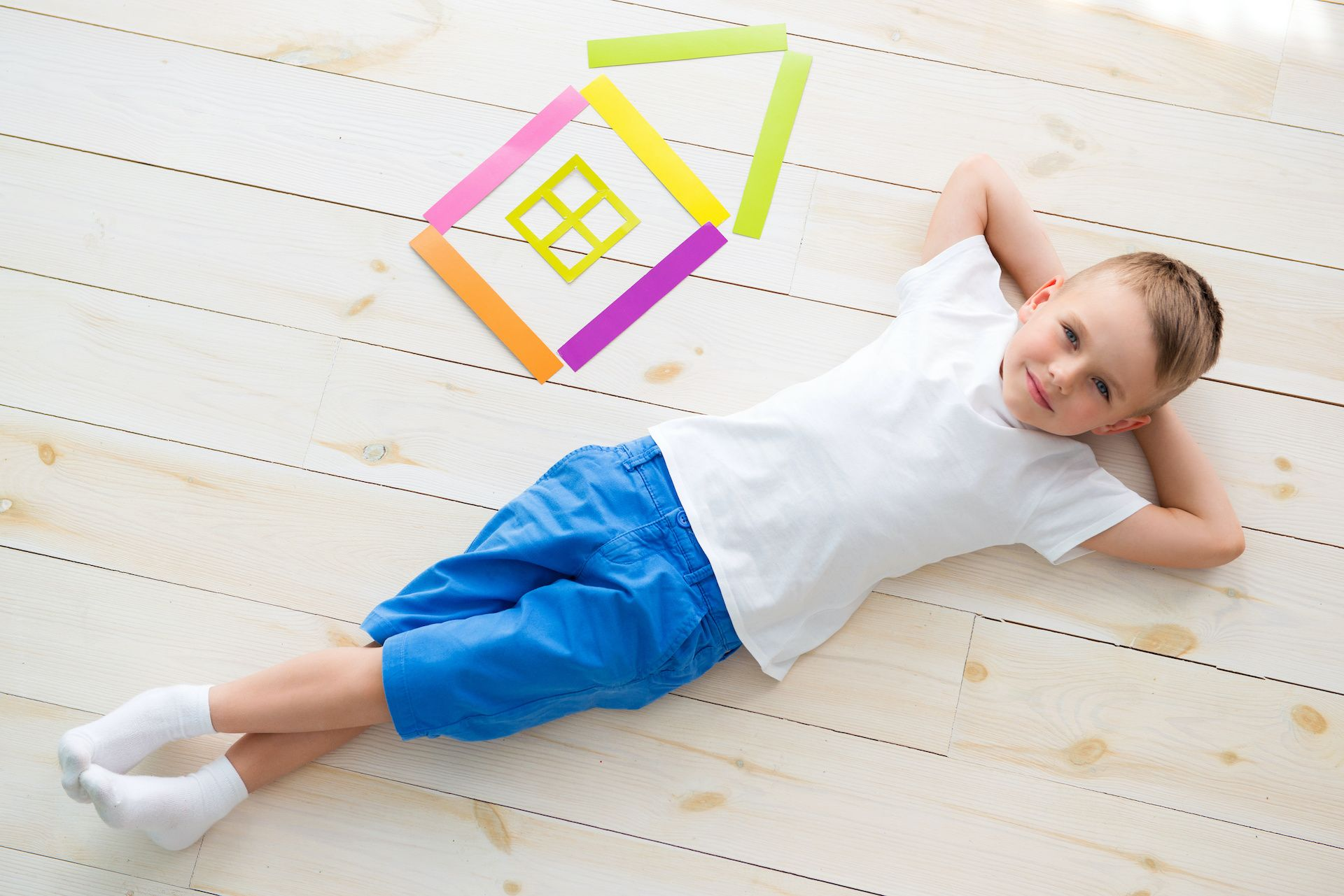 little boy lies on the floor next to a house of colored paper